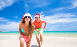 Young couple in santa hats laughing on tropical Royalty Free Stock Photos
