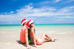 Young couple in santa hats laughing on tropical Stock Images