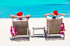 Young couple in Santa hats relaxing on beach during Christmas vacation. Couple in Santa hats relaxing on tropical beach during Christmas vacation Royalty Free Stock Image