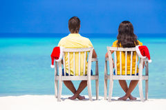 Young couple in Santa hats relaxing on tropical beach during Christmas vacation. Rear view of young couple in Santa hats relaxing on tropical beach during Stock Image