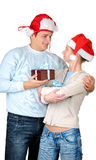 Young couple  in santa's hats holding gift boxes Royalty Free Stock Image