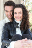 Young couple sat by wall Royalty Free Stock Image