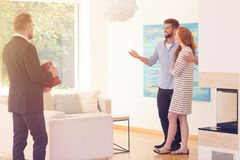 Young couple satisfied with apartment. Young couple satisfied with the interior of an apartment for rent offerred by estate agent Stock Images