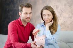 Young couple saves into piggybank Stock Image