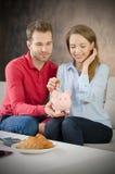 Young couple saves into piggybank Royalty Free Stock Photos