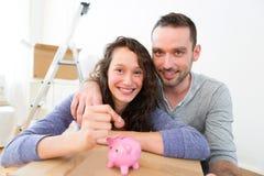 Young couple saving money in a piggy bank Stock Photos