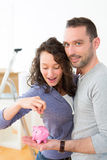 Young couple saving money in a piggy bank Royalty Free Stock Image