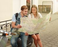 Young Couple with scooter looking at map. Royalty Free Stock Image