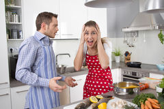 Young couple screaming at home in the kitchen. Young couple crying and screaming at home: trouble under a married couple Stock Image