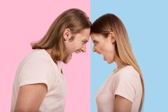 Young couple screaming and pressing their foreheads together. Full of anger. Long-haired young men and his girlfriend pressing their foreheads against one stock photography