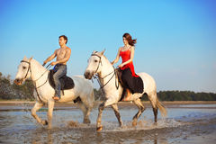 Young couple in the sea on horseback Royalty Free Stock Photos