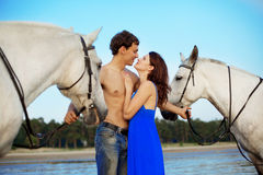 Young couple in the sea with horses Stock Photography
