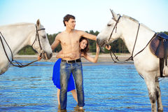Young couple in the sea with horses Stock Photos