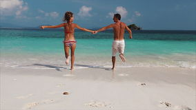 Young couple in the sea. Young couple running into tropical sea stock footage