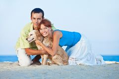 Young couple at sea side playing with their dog. Young couple, summertime, sea side, happy games with their dog Royalty Free Stock Photo