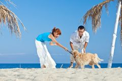 Young couple at sea side playing with their dog. Young couple, summertime, sea side, happy games with their dog Royalty Free Stock Photography