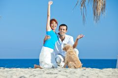 Young couple at sea side playing with their dog. Young couple, summertime, sea side, happy games with their dog Stock Photo