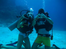 Young couple on the seafloor show different gestures while divin Stock Photo