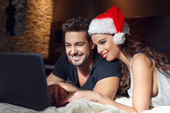 Young couple searching for christmas presents online Stock Image