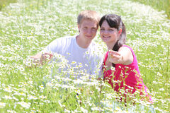 Young couple seat in camomile field Royalty Free Stock Photos