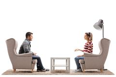 Young couple seated in armchairs having a conversation. Isolated on white background Royalty Free Stock Image