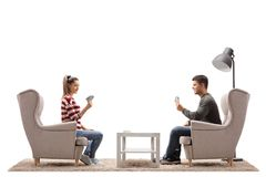 Young couple seated in armchairs playing cards. Isolated on white background royalty free stock photos