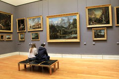 Young couple seated on bench studying priceless masterpieces,The Louvre,Paris,2016. Young couple, seated together on wood bench, admiring priceless masterpieces Stock Photos