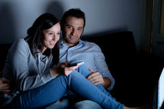Young couple seated on the sofa and watching television Royalty Free Stock Photos