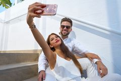Young couple selfie photo with smarphone. In a white stairway outdoor Royalty Free Stock Photography