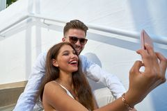 Young couple selfie photo with smarphone. In a white stairway outdoor Royalty Free Stock Images