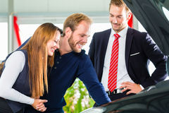 Young Couple and seller with auto in car dealership. Seller or car salesman and clients or customers in car dealership presenting the engine performance of new stock photo