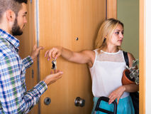 Young couple separating after quarrel. Unhappy couple at the doorway separating and going apart after quarrel Royalty Free Stock Photos