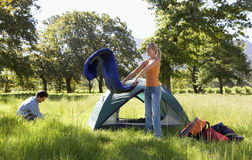 Young couple setting up camp in woodland clearing, woman unravelling rolled-up sleeping bag beside tent, side view Royalty Free Stock Image