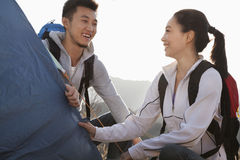 Young couple setting up the tent Stock Images