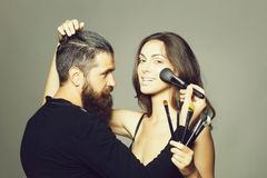 Visagiste bearded man and sexy woman. Young couple of sexy women with pretty smiling face and long brunette hair in black bra on body and handsome bearded men royalty free stock images