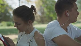 Young couple shake to the beat of music. Man and woman are sitting back to back and listen to music from the headphones. Young people are spending time outdoor stock footage