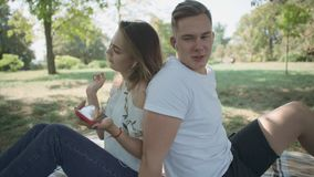 Young couple shake to the beat of music. Man and woman are sitting back to back and listen to music from the headphones. Young people are spending time outdoor stock video footage