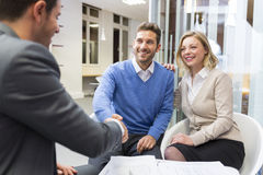 Young couple shaking hand real-estate agent in agency office Royalty Free Stock Image