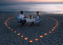 A young couple share a romantic dinner on the beach. A young couple share a romantic dinner with candles heart on the sea sand beach stock photography