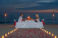 Young couple share a romantic dinner with candles. Torches and way or rose petals on sea sandy beach against sunset - wedding day, proposal of marriage or stock photography