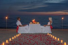 Young couple share a romantic dinner with candles and way or rose. Young couple share a romantic dinner with candles, torches and way or rose petals on sea sandy royalty free stock photography