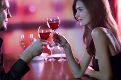 Young couple sharing a glass of red wine in restaurant, celebrat. Ing or on romantic date. Focus on woman Stock Images