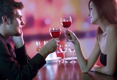 Young couple sharing a glass of red wine in restaurant, celebrat Royalty Free Stock Image