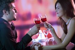 Young couple sharing a glass of red wine in restaurant, celebrat. Ing or on romantic date. Focus on woman with glass Stock Image
