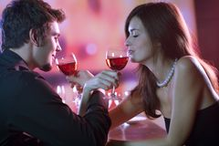 Young couple sharing a glass of red wine in restaurant, celebrat. Ing or on romantic date. Focus on woman with glass Royalty Free Stock Photography