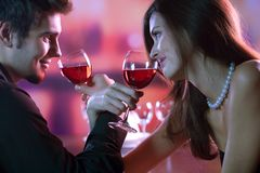 Young couple sharing a glass of red wine in restaurant, celebrat. Ing or on romantic date Royalty Free Stock Photo