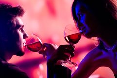 Young couple sharing a glass of red wine in restaurant, celebrat Stock Photography