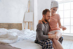 Young couple sharing happy moment together. Can you believe. Brunette of unearthly beauty showing a positive pregnancy test to her husband while sitting on his royalty free stock images