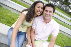 Young couple sharing MP3 player outdoors, smiling, portrait Royalty Free Stock Images