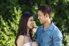 Young couple sharing a pink rose Stock Photo